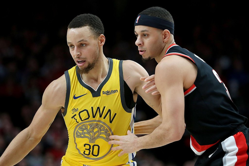 Seth Curry guarding his brother Steph Curry during an NBA game