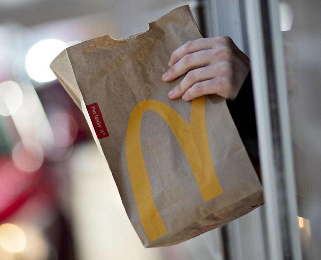 Handing a McDonald's paper bag