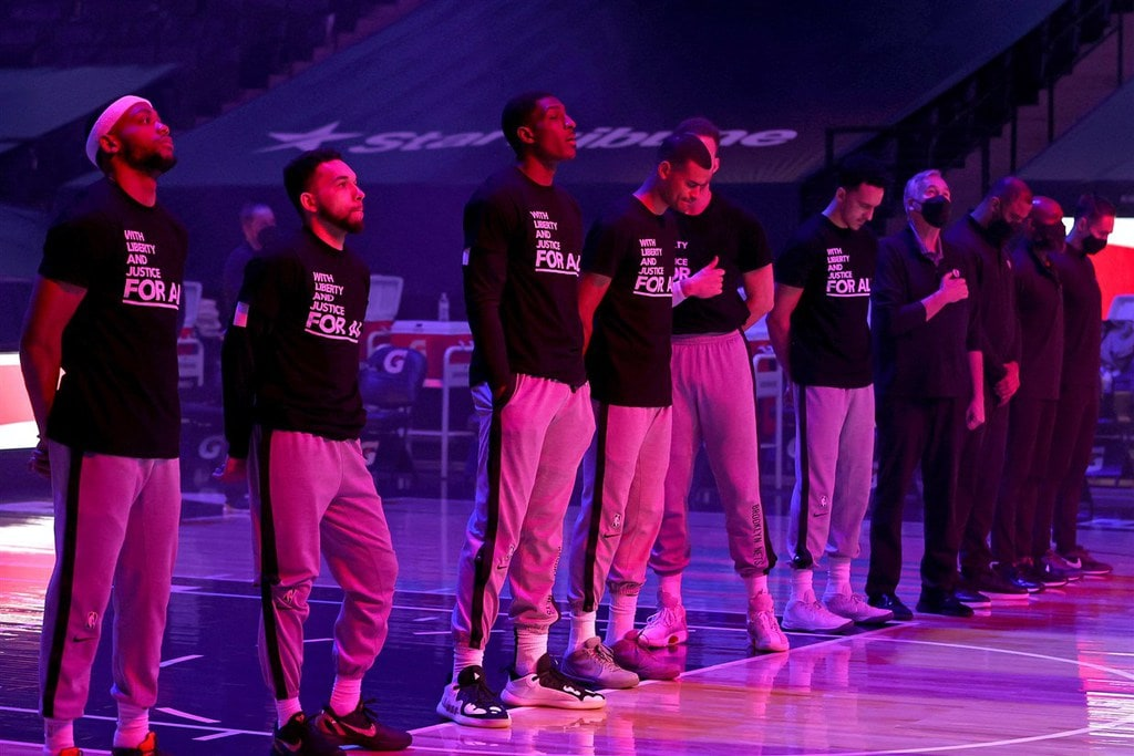 Timberwolves and Nets players during a moment of silence for Daunte Wright wearing matching T-shirts.