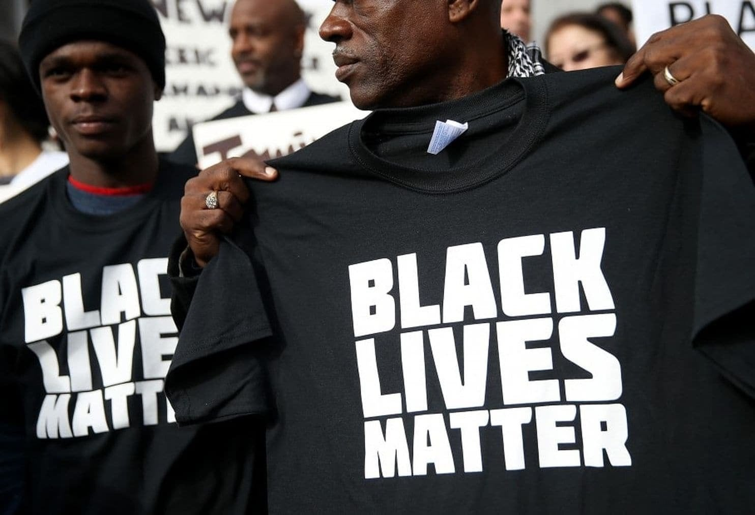 """Man holding a t-shirt with """"Black Lives Matter"""" lettering"""