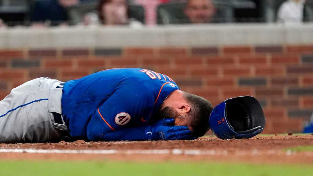 New York Mets player Kevin Pillar, moments after the hit, laying on the ground