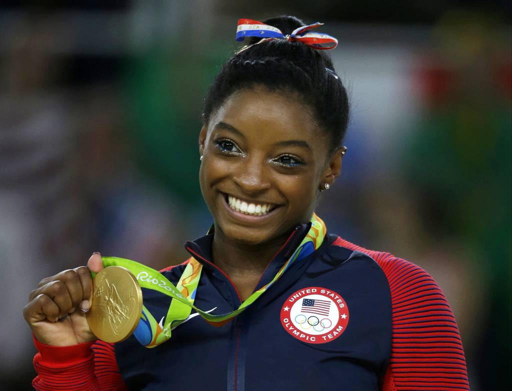 Simone Biles posing with one of the four gold medals she won during the 2016 Summer Olympic Games in Rio.